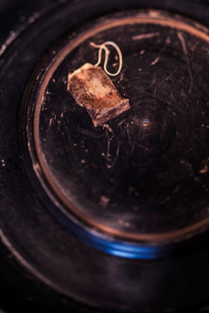 Teebeutel benutzt auf schwarzem Holztablett